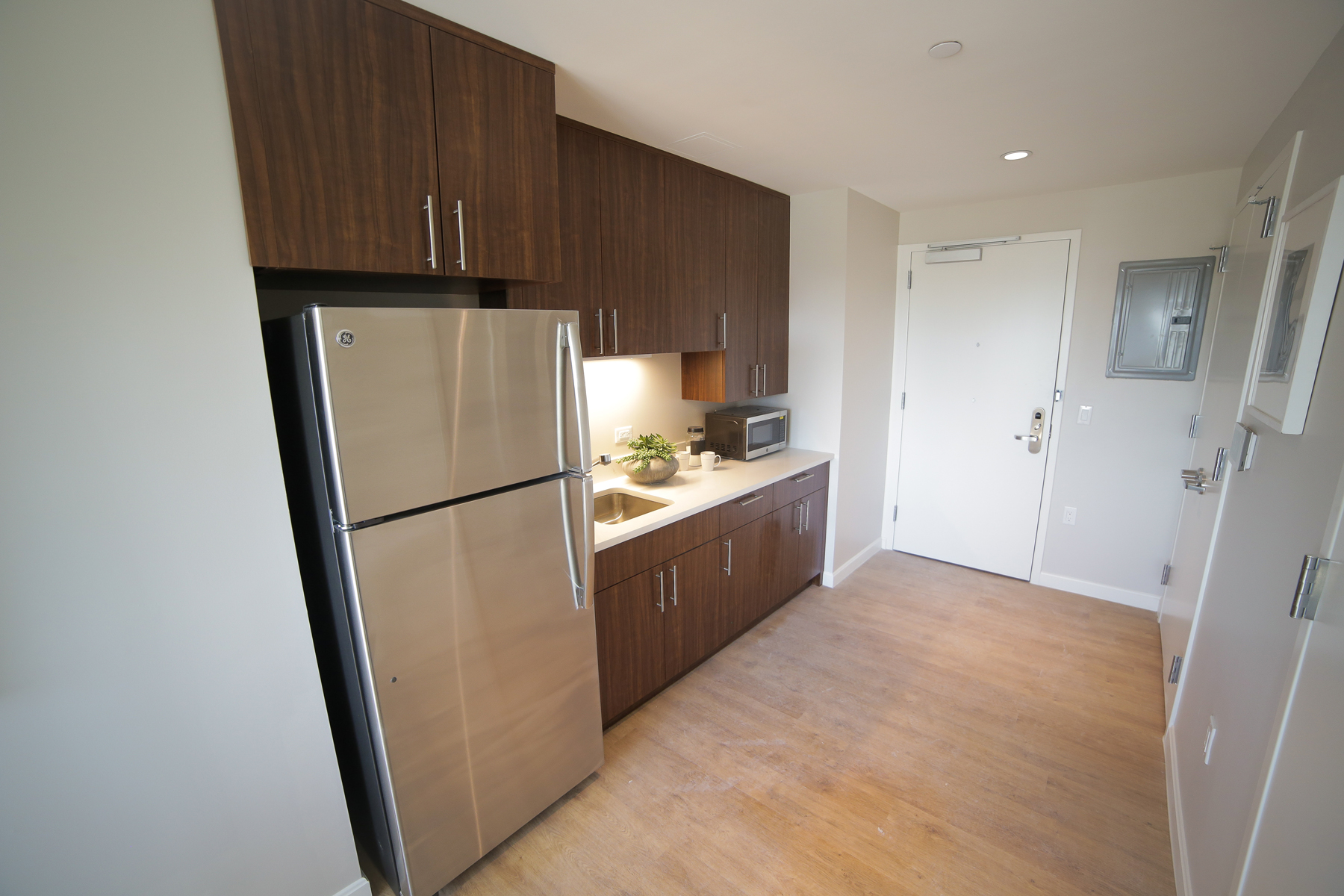 The kitchen of a one-bedroom apartment, featuring stainless steel appliances, hardwood floors, and modern cabinets.