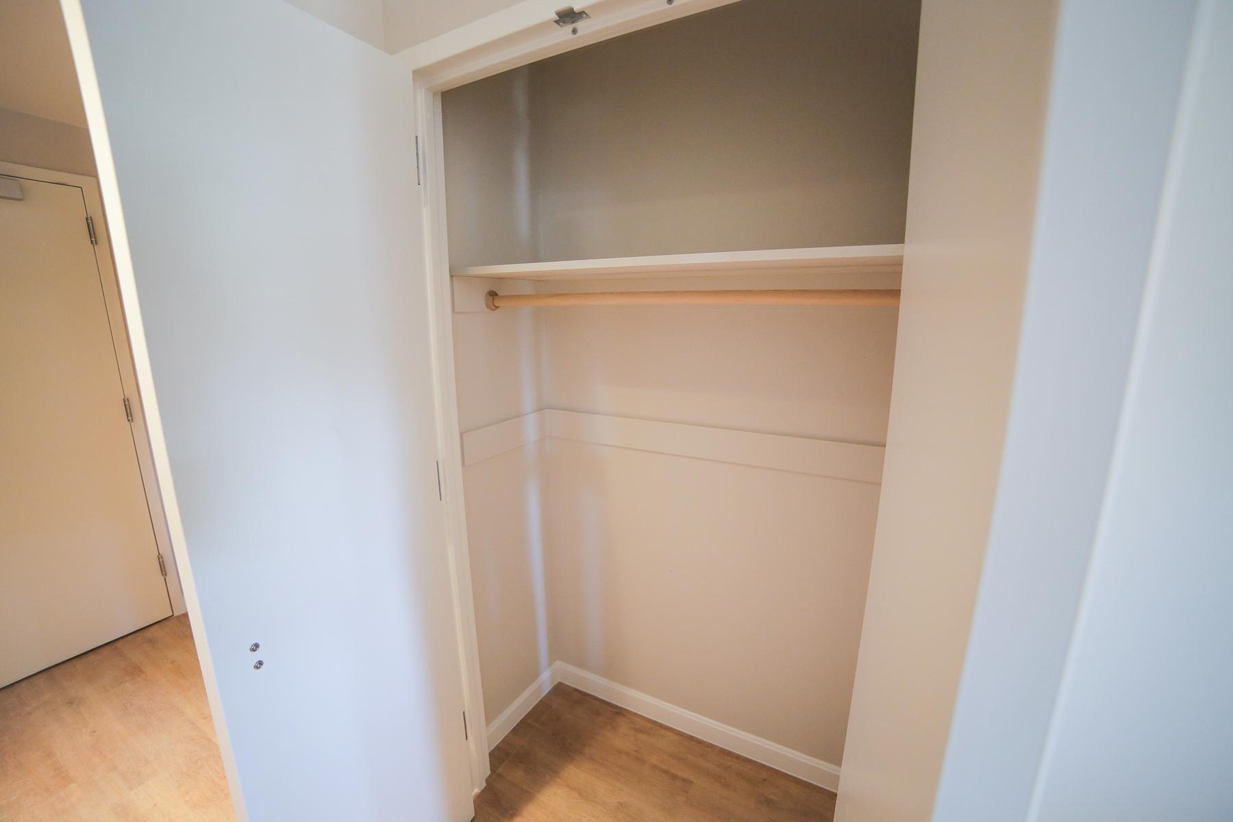 A closet inside of a Studio apartment.