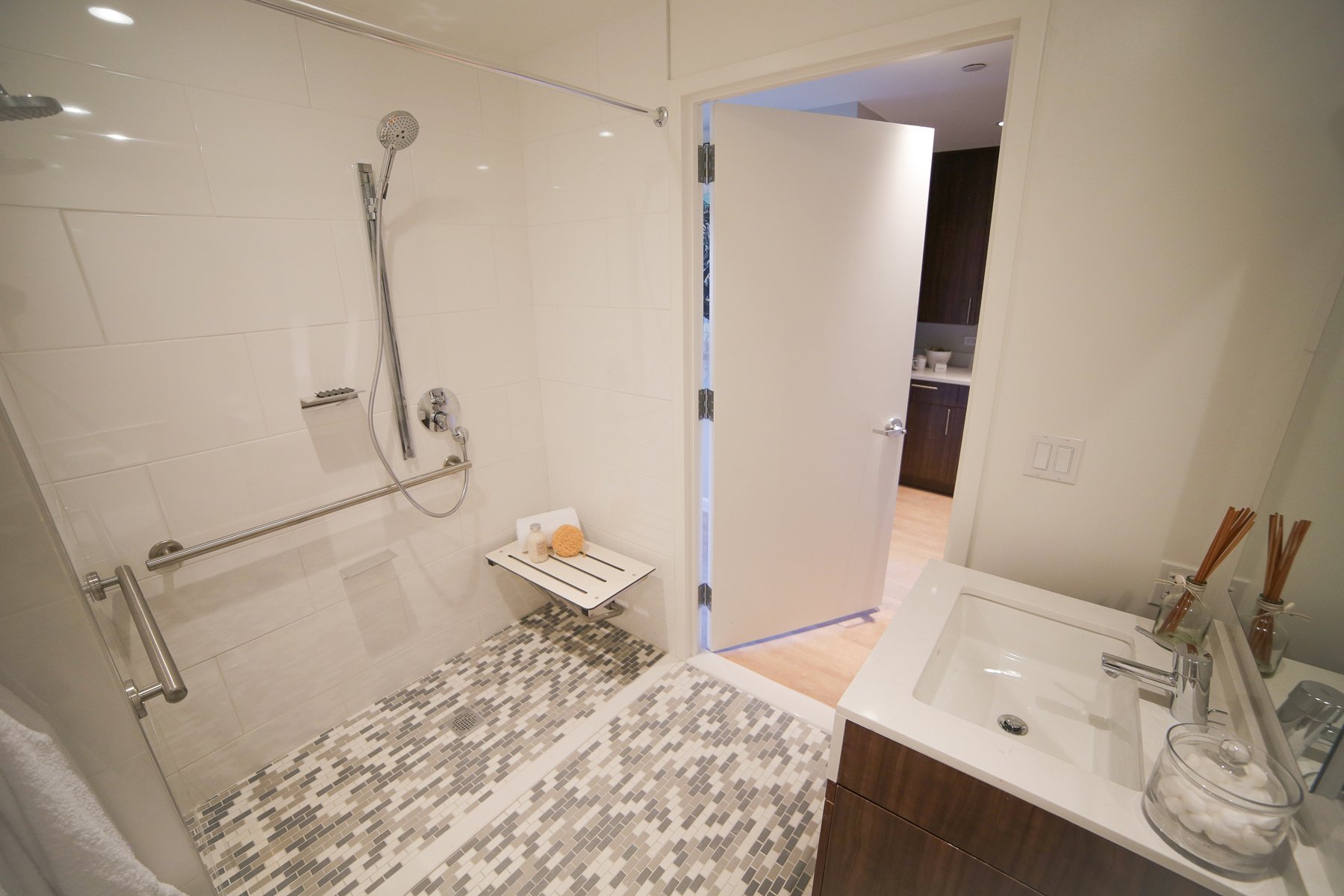 A bathroom featuring a handicap accessible walk-in shower, modern bathroom fixtures, and accessible handrails.